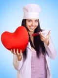 De arts spuit een spuit in het rode hart in stock fotografie