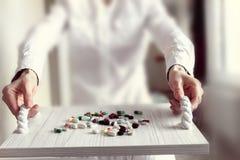 De arts stelt kleurrijke pillen op een wit dienblad voor stock fotografie