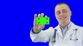 De arts toont een adreskaartje aan Chroma zeer belangrijke achtergrond stock videobeelden