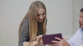 De arts toont een beeld van een ultrasone klank op een tablet aan een zwangere vrouw Een gelukkige toekomstige moeder bewondert e stock video