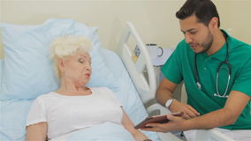 De arts toont iets op zijn tablet aan vrouwelijke patiënt stock video