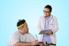De arts toont medische resultaten aan zijn vette patiënt stock foto