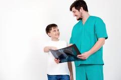 De arts toont röntgenstralen van de patiënt op een witte achtergrond Stock Foto