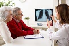 De arts toont resultaten aan oude geduldige röntgenstraal van de longen Royalty-vrije Stock Fotografie