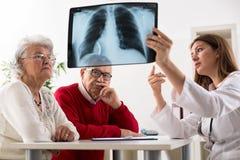 De arts toont resultaten aan oude geduldige röntgenstraal van de longen Stock Fotografie