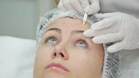 De arts trekt lijnen met teller op geduldig gezicht voor gezichtsplastische chirurgie bij kliniek stock video