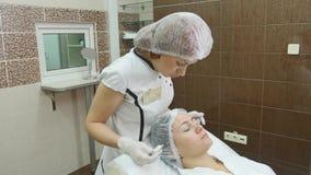 De arts trekt lijnen met teller op geduldig gezicht voor gezichtsplastische chirurgie bij kliniek stock videobeelden