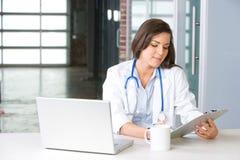 De arts van de vrouw in een modern bureau Stock Afbeeldingen