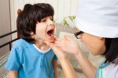 De arts van kinderen kijkt keel van jongen stock afbeelding