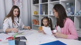 De arts van kinderen schrijft vitaminen een klein meisje voor dat samen met haar moeder aan de ontvangst in een medische kliniek  stock videobeelden
