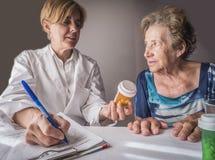 De arts verklaart aan bejaarde dagelijkse dosis medicijn royalty-vrije stock afbeeldingen