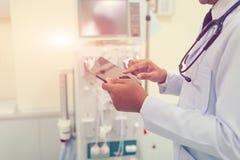 De arts werkt met iPad bij de ruimte van de het ziekenhuisnoodsituatie royalty-vrije stock afbeelding