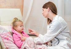 De arts zet een thermometer van een klein meisje in bed Royalty-vrije Stock Fotografie