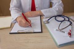 De arts zit in een medisch bureau in de kliniek en schrijft medische geschiedenis Geneeskunde doctor& x27; s werkende lijst Stock Afbeelding