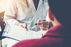 De artsen en de patiënten zitten en spreken Bij de lijst dichtbij het venster stock fotografie
