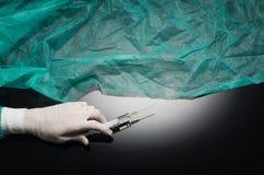 De artsen overhandigen holdingsspuit op zwarte achtergrond met exemplaarruimte Royalty-vrije Stock Afbeeldingen