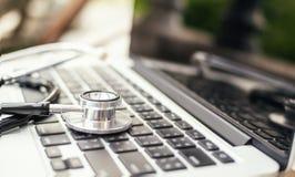 De artsen` s oortelefoons met laptops controleren en controleren FO stock foto