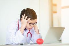De artsenjongen bekeek laptop met een ernstige uitdrukking op whi Stock Afbeeldingen