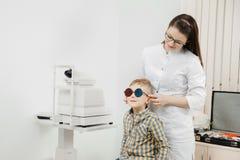 De artsenoftalmoloog controleert de kleurenblindheid van de kindvisie royalty-vrije stock fotografie