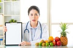 De artsenvoedingsdeskundige met vruchten en holdings leeg klembord viel Royalty-vrije Stock Afbeelding