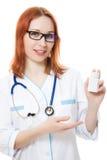 De artsenvrouw die een container van vitaminen houdt Stock Afbeeldingen