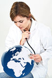 De artsenvrouw onderzoekt wereldbol met haar stethoscoop geïsoleerd o Royalty-vrije Stock Afbeelding