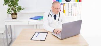 De artsenwerken bij laptop bij zijn bureau in kliniek stock afbeeldingen