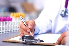 De artsenzitting bij het bureau in het bureau en neemt nota's Stock Afbeelding