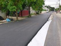 De asfaltweg in een ontwikkelingsproject heeft reeds de helft royalty-vrije stock afbeeldingen