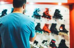 De assortimentsrolschaatsen in opslag winkelen, persoon het kiezen en kopen kleurenrolschaatsen op de gezonde gloed van de backgr royalty-vrije stock afbeeldingen
