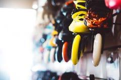 De assortimentsrolschaatsen in opslag winkelen, persoon het kiezen en kopen kleurenrolschaatsen op de gezonde gloed van de backgr stock afbeelding
