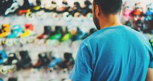 De assortimentsrolschaatsen in opslag winkelen, persoon het kiezen en kopen kleurenrolschaatsen op de gloed van de backgraundzon royalty-vrije stock foto