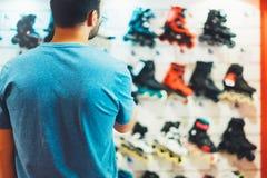 De assortimentsrolschaatsen in opslagwinkel worden geïsoleerd, persoon het kiezen en kopen kleurenrolschaatsen op de gezonde die  stock afbeelding