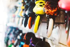 De assortimentsrolschaatsen in opslagwinkel worden geïsoleerd, persoon het kiezen en kopen kleurenrolschaatsen op de gezonde die  stock fotografie