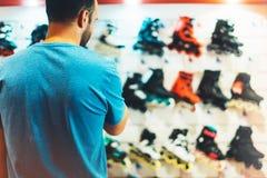 De assortimentsrolschaatsen in opslagwinkel worden geïsoleerd, persoon het kiezen en kopen kleurenrolschaatsen op de gezonde die  royalty-vrije stock foto