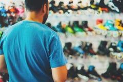 De assortimentsrolschaatsen in opslagwinkel worden geïsoleerd, persoon het kiezen en kopen kleurenrolschaatsen op de gloed die va royalty-vrije stock foto's