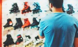 De assortimentsrolschaatsen in opslagwinkel worden geïsoleerd, persoon het kiezen en kopen kleurenrolschaatsen op de gloed die va royalty-vrije stock afbeeldingen