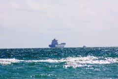 De Atlantische Oceaan in Florida dicht bij zonsondergang met een schip dat een verschepende container is Stock Afbeelding