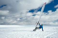 De atleet berijdt een surfplank en skis Stock Foto
