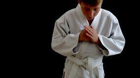 De atleet bevindt zich in een witte kimono U kunt slechts deel van zijn lichaam zien De jongen is girded met een witte riem stock videobeelden