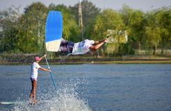 De atleet die van de Wakeboardermens wakeboarding sprongen uitvoeren bij het park van het kabelkielzog royalty-vrije stock fotografie