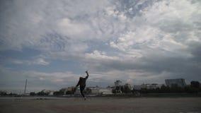 De atleet maakt een veelvoudige salto mortale op de straat stock footage