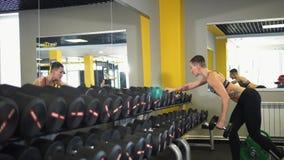 De atleet maakt oefeningen om de bicepsen, de triceps en de achterspieren te versterken stock footage