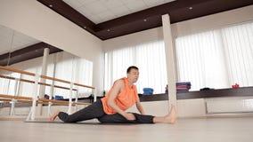 De atleet-mens maakt torsodraaien, zittend op de vloer in de gymnastiek, yogaoefeningen Gezondheid, het leven, flexibiliteit stock videobeelden