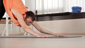 De atleet-mens maakt torsodraaien, zittend op de vloer in de gymnastiek, yogaoefeningen Gezondheid, het leven, flexibiliteit stock footage