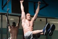 De atleet Performing Hanging Leg heft Oefening op royalty-vrije stock foto