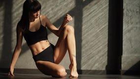 De atleet probeert om oefeningen te doen de spieren van het lichaam tijdens geschiktheid opwarmen stock footage