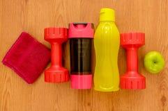 De atleet ` s plaatste met twee roze domoren, groene appple, kleine rode handdoek en twee flessen water, op een rij op houten Stock Fotografie