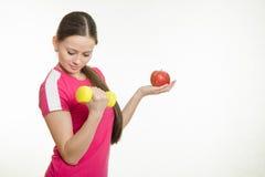De atleet schudt spieren van zijn rechtse holding een appel en een domoor in uw linkerhand Royalty-vrije Stock Afbeelding