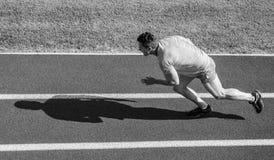 De atleet stelt achtergrond van het stadion de groene gras in werking Agent sportieve vorm in motie Sportlevensstijl en gezondhei royalty-vrije stock foto's